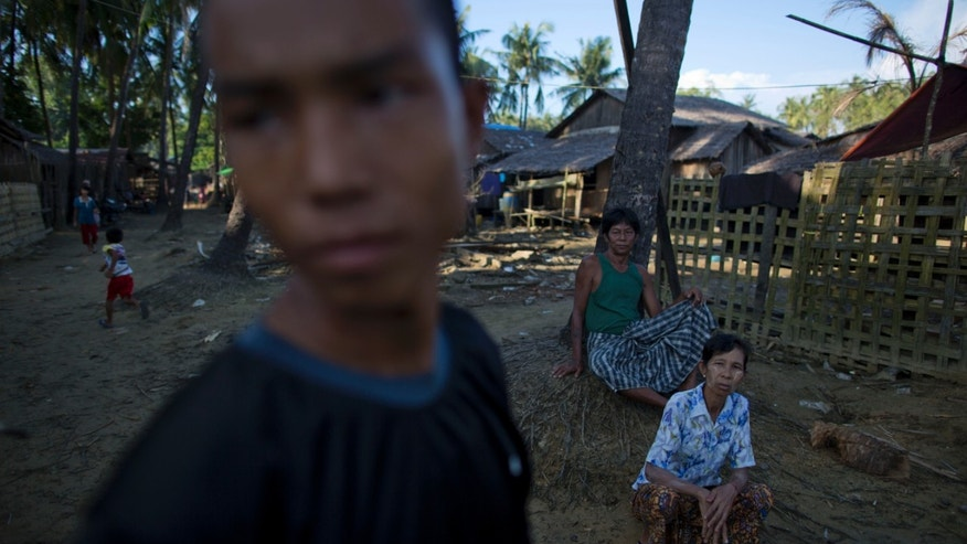 In this Nov. 3, 2013 photo, Min Thu, 17, a run-away boy soldier of Myanmar army, foreground, stands near his father Zaw Win, center, and mother Daw San in Chaung Tha, Irawaddy, Myanmar. Thu disappeared when he was 12 years old, a skinny boy from the wrong side of town who thought he'd stumbled onto the golden ticket. It began when a swaggering, potbellied businessman bumped into Thu at the market, offering him an escape from a neighborhood where the houses are made of lumberyard scraps and the air smells of fish and decay and woodsmoke. It ended with four years in the army. (AP Photo/Gemunu Amarasinghe)