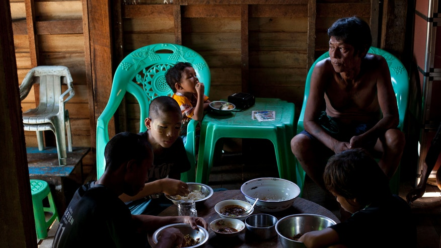 In this Nov. 3, 2013 photo, Min Thu, 17, foreground left, a run-away boy soldier of Myanmar army, eats a meal with his younger brother Ye Min Naing, second left, and others as his father Zaw Win, right, watches in Chaung Tha, Irawaddy, Myanmar. Min, who finally ran away from the army a year ago was one of the thousands of boys who have been swallowed up over the years by Myanmar's army, one of the most feared institutions in the country.  (AP Photo/Gemunu Amarasinghe)