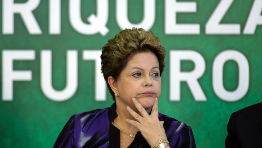 Brazil's President Dilma Rousseff, listens to Petrobras' President Gracias Fortes during the signing ceremony for the first contract of Brazilian Pre-Salt oil field, at the Planalto presidential palace, in Brasilia, Brazil, Monday, Dec. 2, 2013. Brazil has just signed a contract with a consortium of four foreign companies and one Brazilian, for the extraction of its largest oil field to date. (AP Photo/Eraldo Peres)