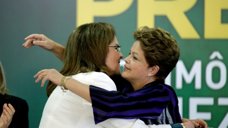 Brazil's President Dilma Rousseff, right, embraces Brazil's Petrobras President Graca Fortes, during the signing ceremony for the first contract of Brazilian Pre-Salt oil camp, at the Planalto presidential palace, in Brasilia, Brazil, Monday, Dec. 2, 2013. Brazil has just signed a contract with a consortium of four foreign companies and one Brazilian, for the extraction of its largest oil field to date. (AP Photo/Eraldo Peres)