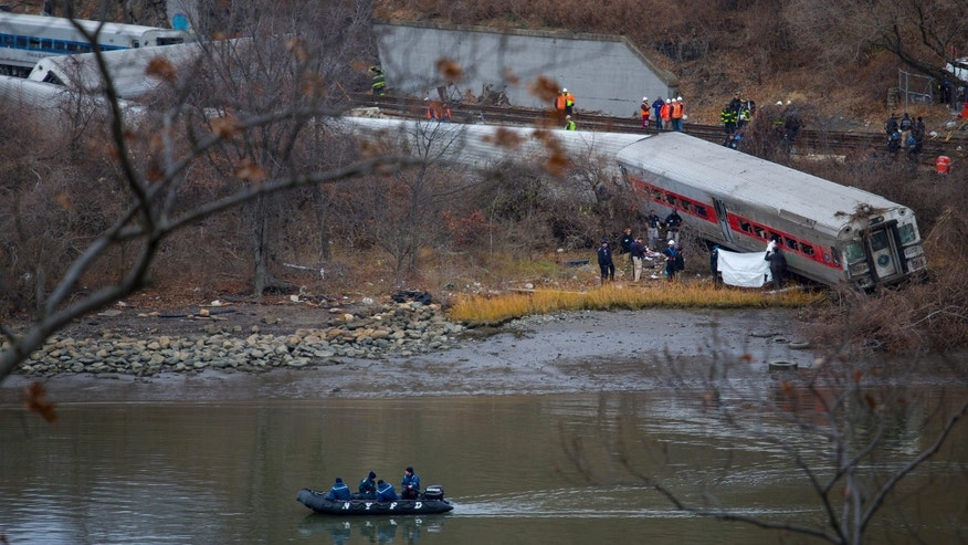 Viewed from Manhattan, first responders and others work near a victim next to a derailed Metro North passenger train in the Bronx borough of New York, Sunday, Dec. 1, 2013. The train derailed on a curved section of track coming to rest just inches from the water and causing multiple fatalities and dozens of injuries, authorities said. Metropolitan Transportation Authority police say the train derailed near the Spuyten Duyvil station. (AP Photo/Craig Ruttle)