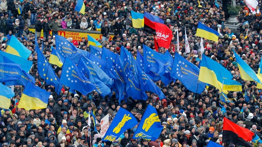 Demonstrators wave flags as they gather during a rally in downtown Kiev, Ukraine, on Sunday, Dec. 1, 2013. As many as 100,000 demonstrators chased away police to rally in the center of Ukraine's capital on Sunday, defying a government ban on protests on Independence Square, in the biggest show of anger over the president's refusal to sign an agreement with the European Union. (AP Photo/Sergei Grits)