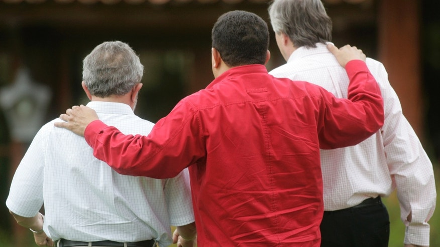 FILE - In this Jan 19, 2006 file photo, Venezuela's President Hugo Chavez, center, embraces Brazil's President Luiz Inacio Lula Da Silva, left, and Argentina's President Nestor Kirchner, in Brasilia, Brazil. The days of geopolitical chest thumping, best captured when Chavez in 2006 laid out plans to build a pipeline stretching across South America, are a fast-fading memory.  (AP Photo/Silvia Izquierdo, File)