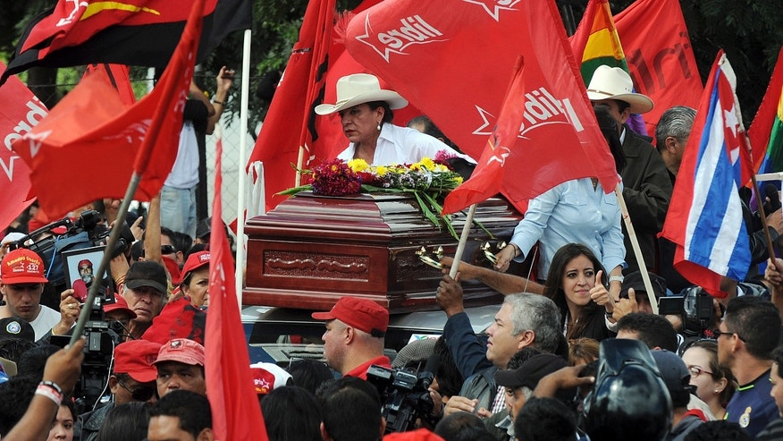 Presidential candidate Xiomara Castro rides on the roof of a car with a coffin containing the body of a supporter that was killed a day earlier by alleged criminals during a protest march in the capital city of Tegucigalpa, Honduras, Sunday, Dec. 1, 2013. Castro called for her supporters to pour out in the streets to demand a vote-by-vote recount of last Sunday's election  a move that could mean further political instability for this poor Central American country. (AP Photo/Fernando Antonio)