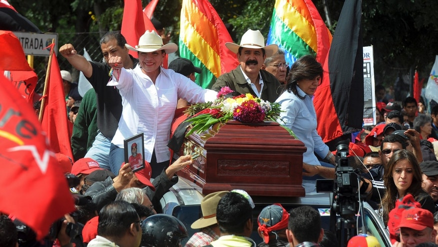Presidential candidate Xiomara Castro, left, and her husband, Manuel Zelaya, ride on the roof of a car with a coffin containing the body of a supporter that was killed a day earlier by alleged criminals during a protest march in the capital city of Tegucigalpa, Honduras, Sunday Dec. 1, 2013. Castro called for her supporters to pour out in the streets to demand a vote-by-vote recount of last Sunday's election  a move that could mean further political instability for this poor Central American country. Castro's husband, former President Manuel Zelaya, was ousted in a 2009 coup that left the country polarized.(AP Photo/Fernando Antonio)