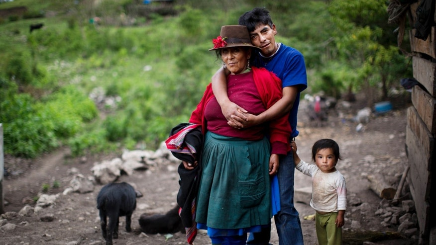 In this Nov. 12, 2013 photo, Aurelia Castro is embraced by her son Raul as his daughter stands by his side. They are posing in their front yard  in the district of Chungui, Peru. Aurelia's first husband was killed in 1984 when the couple tried to escape from soldiers who accused villagers of collaborating with Shining Path rebels. (AP Photo/Rodrigo Abd)