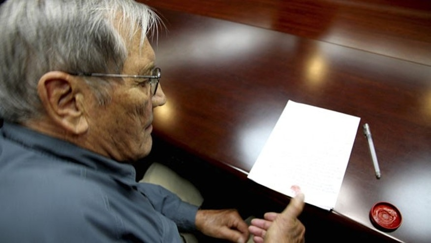 In this Nov. 9, 2013 photo released by the Korean Central News Agency (KCNA) and distributed Nov. 30, 2013 by the Korea News Service, U.S. citizen Merrill Newman, 85, applies his thumb print to a document which North Korean authorities say was an apology which Newman wrote and read in North Korea. (AP/KCNA)