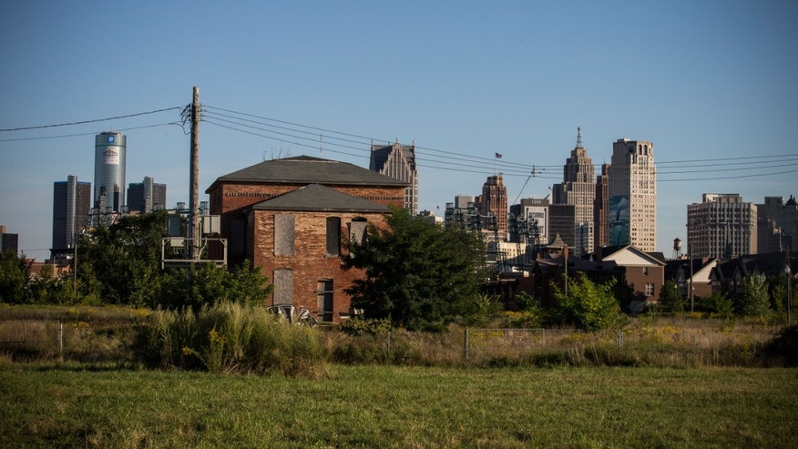 An abandoned home is seen with the Detroit skyline in the background on September 5, 2013 in Detroit, Michigan.