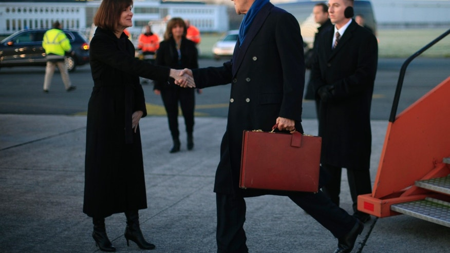 US Secretary of State John Kerry, right, is greeted on the tarmac by U.S. Ambassador to Belgium Denise Bauer, left, upon his arrival in Brussels, Belgium, Tuesday, Dec. 3, 2013. Kerry traveled to Belgium to attend the annual meeting of NATO foreign ministers. (AP Photo/Pablo Martinez Monsivais, Pool)