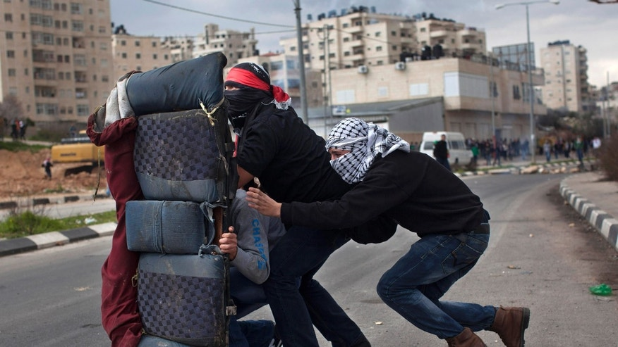 FILE - In this Feb. 19, 2013 photo, masked Palestinians use a rear car seat as a shield during a protest to support Palestinian prisoners, outside Ofer, an Israeli military prison near the West Bank city of Ramallah. Senior Palestinians say the diplomatic pressure that produced the nuclear deal with Iran, world powers negotiating jointly and wielding the stick of sanctions, should now be applied to the long-festering Israeli-Palestinian conflict. (AP Photo/Bernat Armangue, File)