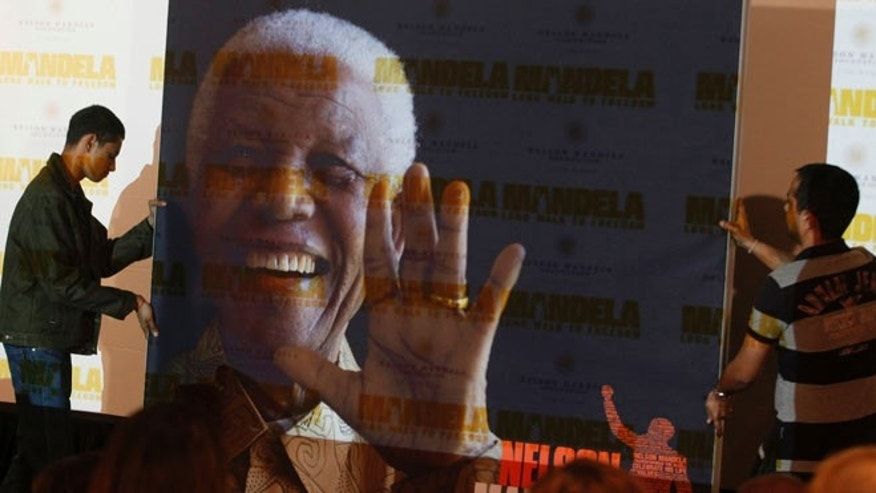"Nov. 2, 2013: In this file photo, a giant poster of Nelson Mandela is moved to center stage at a news conference held to promote the newly released film ""Mandela: Long Walk To Freedom,"" in Johannesburg."