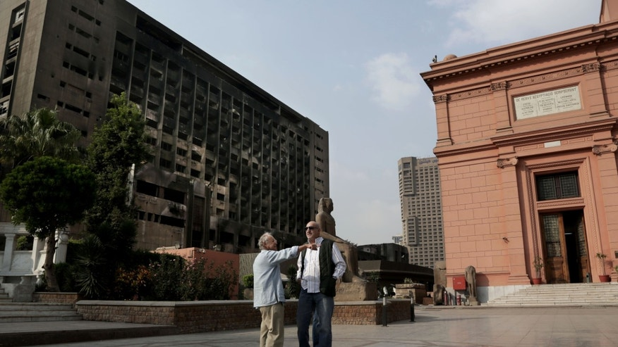 In this Wednesday, Oct. 30, 2013 photo,  tourists chat with the nearby burned headquarters of the former ruling National Democratic Party, background left, in the Egyptian Museum near Tahrir Square in Cairo, Egypt. The 111-year-old museum, a treasure trove of pharaonic antiquities, has long been one of the centerpieces of tourism to Egypt. But the constant instability since the 2011 uprising that toppled autocrat Hosni Mubarak has dried up tourism to the country, slashing a key source of revenue. Moreover, political backbiting and attempts to stop corruption have had a knock-on effect of bringing a de facto ban on sending antiquities on tours to museums abroad, cutting off what was once a major source of funding for the museum. (AP Photo/Nariman El-Mofty)