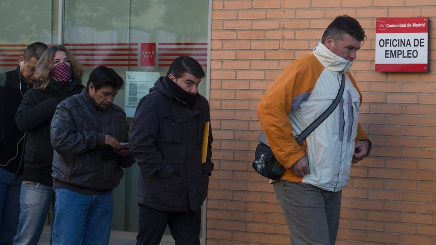 People queue to enter an unemployment registry office in Madrid, Spain, Tuesday, Dec. 3, 2013. Official figures show the number of people registered as unemployed in Spain fell by a little under 2,500 in November, the first drop during the month since the current system was introduced 1997. The decline provided further evidence that the Spanish economy might be picking up after more than two years of recession, which only ended in the third quarter. Still, Spain is still suffering from mass unemployment, with around 4.8 million people out of work. That represents around 26 percent of its total workforce. Only Greece has a higher unemployment rate in the 17-country eurozone. (AP Photo/Paul White)