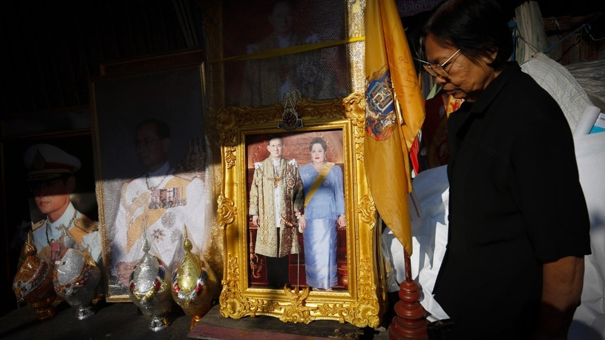 A woman walks near a portrait of Thai King Bhumibol Adulyadej and Queen Sirikit on display, in Bangkok, Thailand, Wednesday, Dec. 4, 2013. Protesters intent on toppling Thailand's democratically elected prime minister plan to press their struggle again Wednesday with a peaceful march on Bangkok's national police headquarters, one day after a sudden truce in honor of the king's birthday this week ended a spate of increasingly fierce street fighting. (AP Photo/Vincent Thian)
