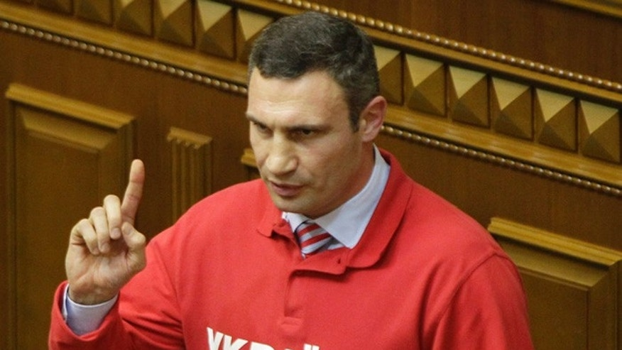 "Chairman of the Ukrainian opposition party Udar (Punch) and WBC Heavyweight Champion boxer Vitali Klitschko, speaks to lawmakers in Kiev, Ukraine. The words emblazoned on the shirts read, ""Ukraine is Europe."" (AP Photo/Sergei Chuzavkov)"