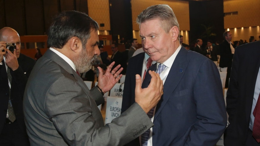 India's Trade Minister Anand Sharma , left, talks with EU Trade Commissioner Karel De Gucht, right, during the opening of the Ninth Ministerial Conference of the World Trade Organisation (WTO) in Bali, Indonesia, Tuesday, Dec 3,  2013. (AP Photo/Achmad Ibrahim)