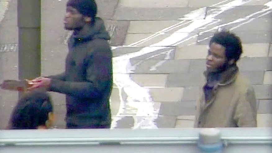 In this photo made from CCTV and released by the Metropolitan Police on Tuesday, Dec. 3, 2013,  Michael Adebolajo and Michael Adebowale  speak to a member of the public near to the Woolwich Barracks in London in May 2013. The footage was shown in court during the trial of Michael Adebolajo, 28, and Michael Adebowale, 22, who stand accused of the murder of Fusilier Lee Rigby. Rigby of the Royal Regiment of Fusiliers, was attacked and killed by two men near the barracks. Two men ran him down with a car, then used knives and a cleaver to stab and hack him to death.  (AP Photo / Metropolitan Police)   UNITED KINGDOM OUT NO SALES NO ARCHIVE