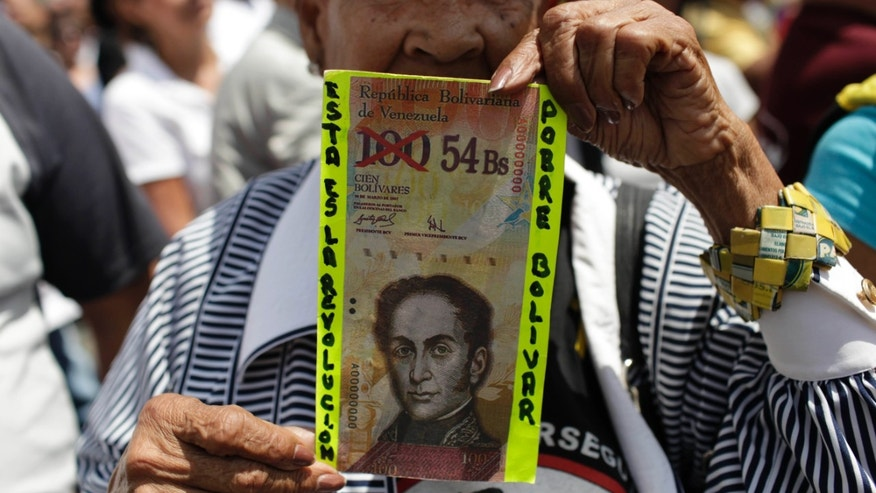 "FILE - In this Feb. 23, 2013 file photo, an anti-government protester in Caracas holds up a fake Venezuelan banknote that reads in Spanish, ""This is the revolution. Poor Bolivar,"" with the value of 100 crossed out and 54 written next to it. Venezuelans have been scrambling for dollars as their bolivar currency is in free fall, selling on the black market for a tenth its official value. In response, the government is trying to block access to websites that Venezuelans use to track the black market exchange rate. (AP Photo/Ariana Cubillos, File)"