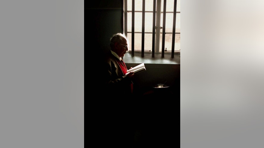 FILE - In this Aug. 12, 1999 file photo, Ahmed Kathrada reads from a just-published book of his prison correspondence in the cell where Nelson Mandela was imprisoned on Robben Island, near Cape Town, South Africa. Kathrada was one of seven men sentenced with Mandela to life in prison for sabotage and plotting to overthrow the white government in what was known as the Rivonia treason trial.  South Africa's president Jacob Zuma says, Thursday, Dec. 5, 2013, that Mandela has died. He was 95.  (AP Photo/Denis Farrell, File)