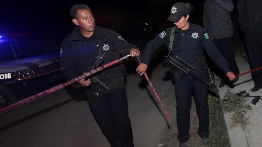 Dec. 4, 2013: Police agents cordon off an area in the village of Hueypoxtla, Mexico.