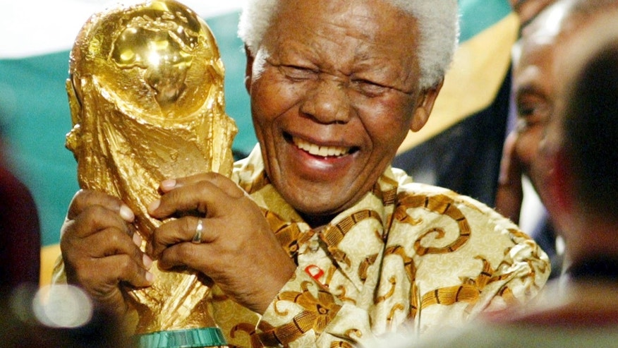 FILE - In this May 15, 2004 file photo, former South African President Nelson Mandela lifts the World Cup trophy in Zurich, Switzerland, after FIFA's executive committee announced that South Africa would host the 2010 FIFA World Cup soccer tournament. Mandela was pivotal in helping the country win the right to host the tournament. South Africa's President Jacob Zuma said, Thursday, Dec. 5, 2013, that Mandela has died. He was 95. (AP Photo/Michael Probst, File)