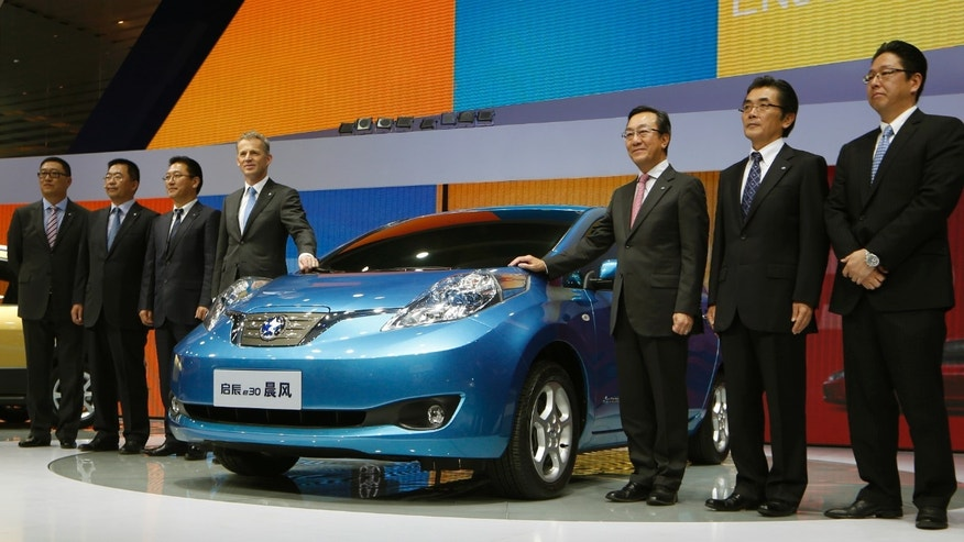 In this Thursday, Nov. 21, 2013 photo, officials pose beside a Venucia e30 electric car created by the joint venture of Dongfeng and Nissan at the company's booth during the Guangzhou Auto Show in China's southern city of Guangzhou. Venucia is a leader in the latest twist in the world's biggest auto market: Chinese brands created by global automakers with local partners to sell foreign cachet at lower prices. Most ambitious are Nissan and General Motors Co. Their local brands have rolled out ultra-low-cost models to make deeper inroads into China, especially in the countryside, home to 700 million people. (AP Photo/Kin Cheung)