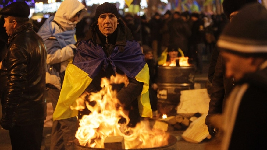 "Protesters warm themselves by a fire in Independent Square in Kiev, Ukraine, Wednesday, Dec. 4, 2013. Thousands of people from different places of Ukraine are gathered in Kiev's Independence Square. As the cry for revolution grows louder from Ukrainian protesters rallying for closer ties with Europe, the Kremlin is eager to stave off copycat efforts in Russia. State media are casting the protesters in Kiev as ""professional revolutionaries"" sponsored by the West and bent on violently toppling the government. (AP Photo/Sergei Chuzavkov)"