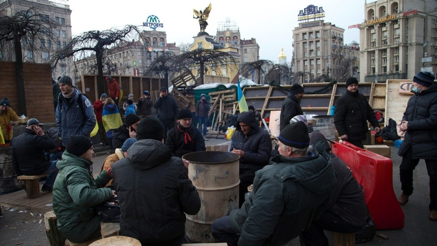 Protesters gather around a fire in a metal bin and eat food distributed for free, at the central Independence Square in Kiev, Ukraine, on Wednesday, Dec. 4, 2013. A resolution to Ukraine's political turmoil remained elusive as thousands of people continued rallying on Kiev's Independence Square and besieging key government buildings. (AP Photo/Ivan Sekretarev)