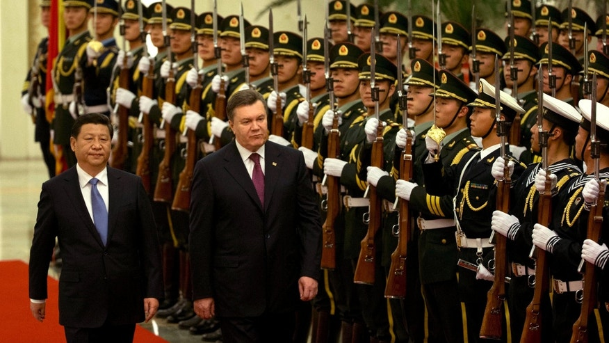 Ukraine's President Viktor Yanukovych, center,  walks with Chinese President Xi Jinping, left,  during a welcome ceremony at the Great Hall of the People in Beijing, China, Thursday, Dec. 5, 2013. Ukraine's embattled president is in China for an official visit while his opponents conduct massive protests at home sparked by his decision to ditch a significant treaty with the European Union after strong pressure from Russia.(AP Photo/Ng Han Guan)