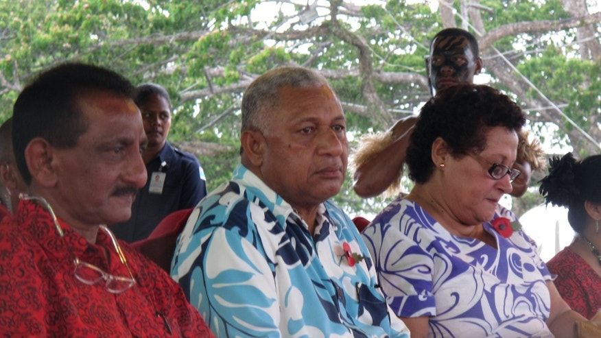 In this Nov. 7, 2013 photo, Fiji's Prime Minister Voreqe Bainimarama, center, attends the opening of a picnic park in Suva, Fiji. Seven years after seizing power in a military coup, Bainimarama, the 59-year-old former naval officer, who also goes by the name Frank, has promised to hold democratic elections in this South Pacific island nation of 900,000. More than half a million Fijians have registered to vote, hoping to end a quarter-century of turmoil. The international community, which imposed sanctions after the coup, has offered a cautious welcome. (AP Photo/Nick Perry)
