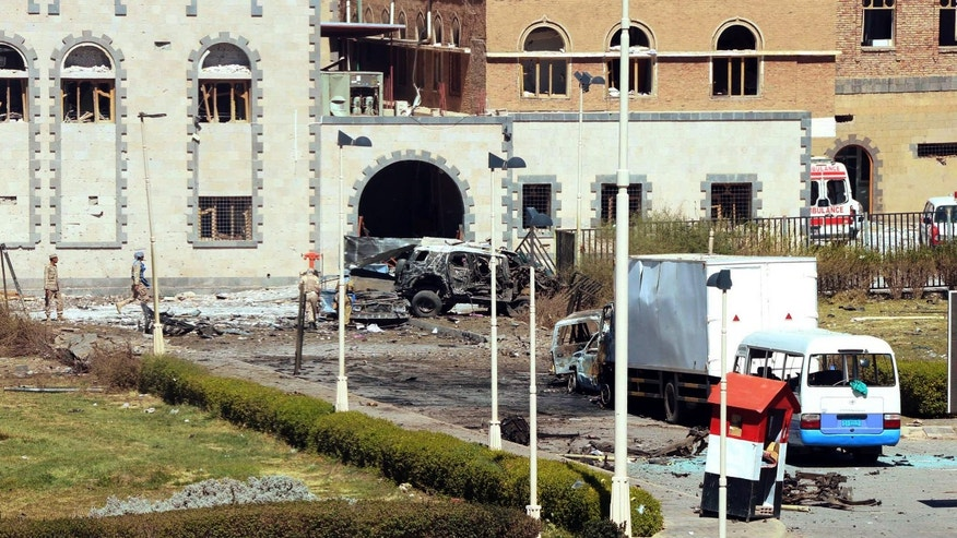 In this photo provided by Yemen's Defense Ministry, security forces are on the scene after an explosion at the Defense Ministry complex in Sanaa, Yemen, Thursday, Dec. 5, 2013. A suicide car bomber struck Yemen's Defense Ministry Thursday, killing more than a dozen soldiers and paving the way for a carload of gunmen wearing army uniforms to storm the heavily guarded compound in the capital of Sanaa, military and hospital officials said. (AP Photo/Yemen Defense Ministry)