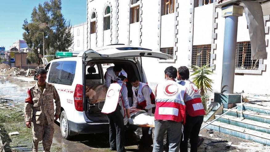 This photo provided by Yemen's Defense Ministry shows paramedics loading a victim into an ambulance after an explosion at the Defense Ministry complex in Sanaa, Yemen, Thursday, Dec. 5, 2013. A suicide car bomber struck Yemen's Defense Ministry Thursday, killing more than a dozen soldiers and paving the way for a carload of gunmen wearing army uniforms to storm the heavily guarded compound in the capital of Sanaa, military and hospital officials said. (AP Photo/Yemen Defense Ministry)
