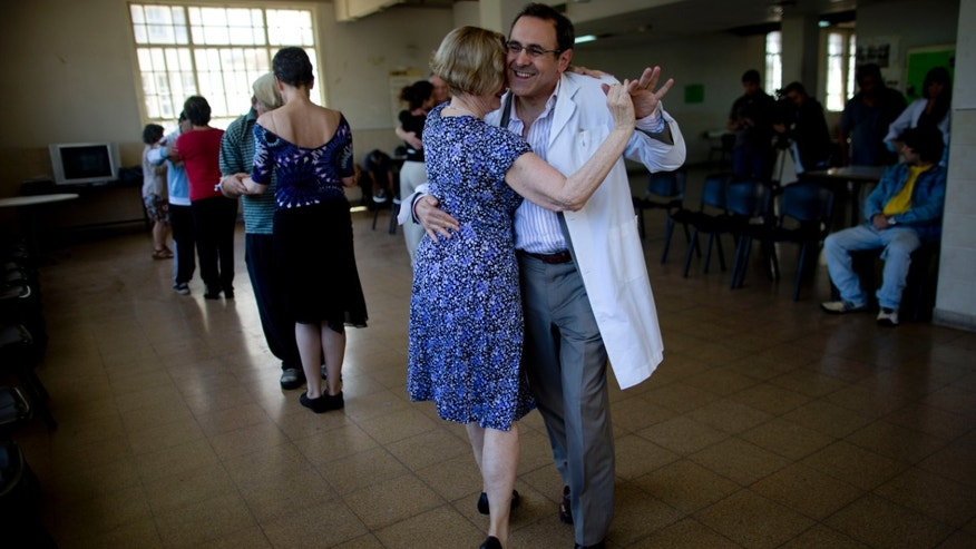 "In this Wednesday, Nov. 13 photo, Dr. Guillermo Honig, right, dances tango with Christine Eydeux, of France, during the ""All of us are crazy for tango"" program at the psychiatric Hospital Borda in Buenos Aires, Argentina. Eydeux says, that in the past five years, every time she visits Argentina, she attends the Wednesday program, that meets twice a month. Because of her frequent attendance, she was named godmother of the program. (AP Photo/Natacha Pisarenko)"