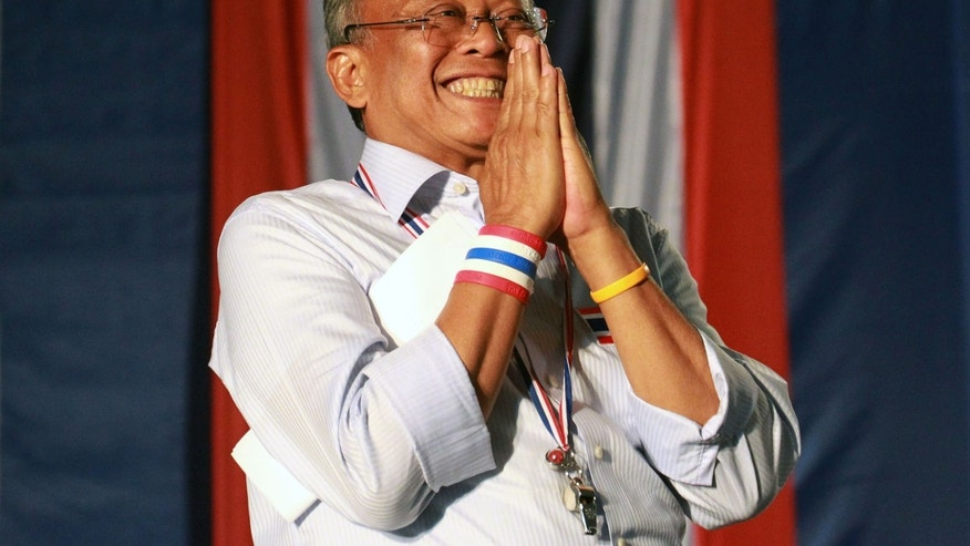 "Thai protest leader Suthep Thuagsuban gives a Thai traditional way of greeting ""wai"" to his supporters during an anti-government rally at the government complex in Bangkok, Thailand, Friday, Dec. 6, 2013. The truce between Thailand's political rivals held in Bangkok on Friday, amid more ceremonies in honor of the king's birthday, while the leader of the protest movement who has vowed to overthrow the government planned to announce his next move. (AP Photo/Wason Wanichakorn)"