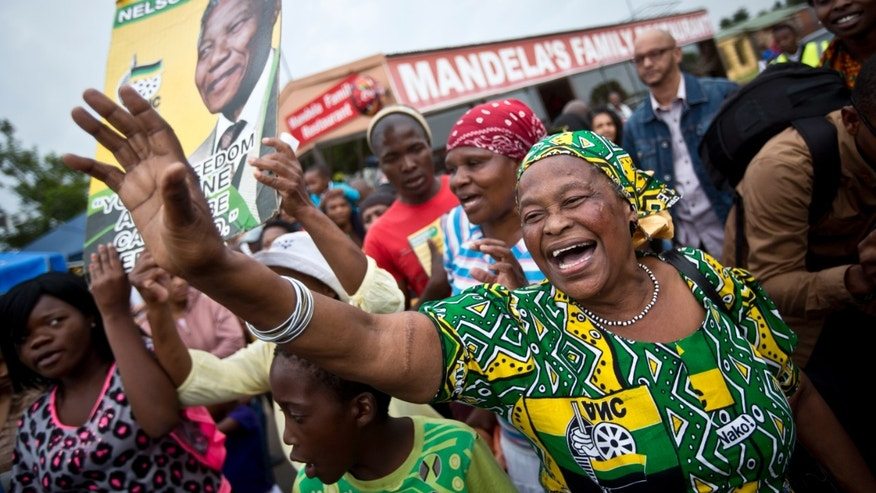 Mourners sing and dance to celebrate the life of Nelson Mandela, in the street outside his old house in Soweto, Johannesburg, South Africa, Friday, Dec. 6, 2013. Flags were lowered to half-staff and people in black townships, in upscale mostly white suburbs and in South Africa's vast rural grasslands commemorated Nelson Mandela with song, tears and prayers on Friday while pledging to adhere to the values of unity and democracy that he embodied. (AP Photo/Ben Curtis)
