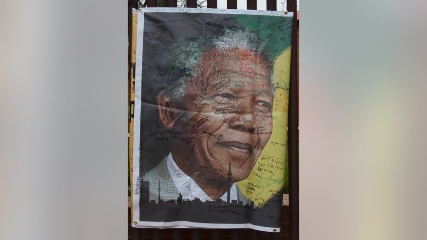 A giant signed poster with messages of support is attached to the former Soweto home, turned museum, of former South African president Nelson Mandela, Soweto, South Africa, Friday Dec. 6 2013. Mandela passed away Thursday night after a long illness. He was 95. As word of Mandela's death spread, current and former presidents, athletes and entertainers, and people around the world spoke about the life and legacy of the former South African leader. (AP Photo/Athol Moralee)