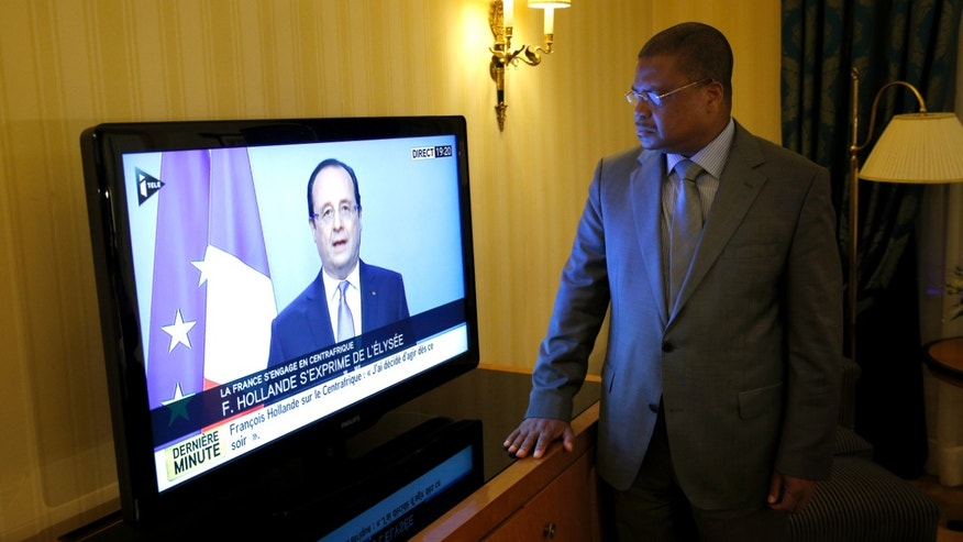 "Prime Minister of the Central African Republic Nicolas Tiangaye watches French President Francois Hollande on TV, as he announces he would double the number of troops in the former French colony, possibly within hours, in Paris, Thursday, Dec. 5, 2013. In his first reaction to the French move, Tiangaye told The Associated Press that he sees it ""very positively"" and that he had wanted a ""firm reaction from France.""  The U.N. Security Council authorized an intervention force to prevent a bloodbath between Christians and Muslims, as fighting swept through the capital of Central African Republic on Thursday, leaving nearly one hundred people dead and posing the biggest threat yet to the country's new government.  (AP Photo/Christophe Ena)"