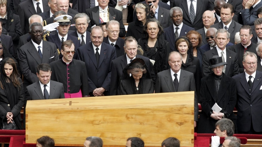 FILE - In this April 8, 2005 file photo, the coffin containing the body of Pope John Paul II passes world leaders, including King Abdullah II and Queen Raina of Jordan, left, King Juan Carlos and Queen Sofia of Spain, center, Queen Margarethe and Prince Consort Henrik, right, U.S. President George W. Bush and first lady Laura Bush, second row, right, Former U.S. President George H.W. Bush, second row center, and French President Jacques Chirac after a funeral mass in St.Peter's Square at the Vatican. Pope John Paul II's funeral is among the sweeping funerals in recent decades that drew the world's attention, and its leaders. (AP Photo/Andrew Medichini, File)