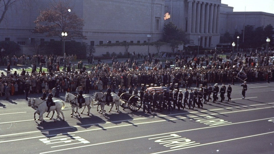 """FILE - In this Nov. 25, 1963 file photo, the caisson bearing the flag-draped coffin of President John F. Kennedy moves in procession down Pennsylvania Avenue, in Washington, en route to Arlington National Cemetery. Kennedy's funeral was attended by """"28 presidents, prime ministers and kings."""" As the horse-drawn coffin moved through Washington, """"streets were lined by hundreds of thousands of people, many of them weeping.""""  (AP File Photo)"""