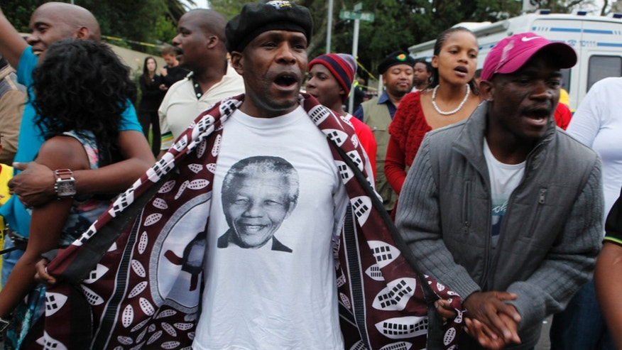 A man wearing a T-shirt with a portrait of former president Nelson Mandela leads a group of mourners as they sing and dance outside the Johannesburg home of Mandela Friday, Dec. 6, 2013 after the freedom fighter passed away Thursday night after a long illness. (AP Photo/Denis Farrell)