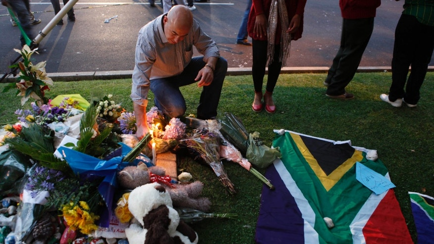 A man lights a candle outside the Johannesburg home of former president Nelson Mandela Friday, Dec. 6, 2013 after Mandela passed away Thursday night after a long illness. (AP Photo/Denis Farrell)