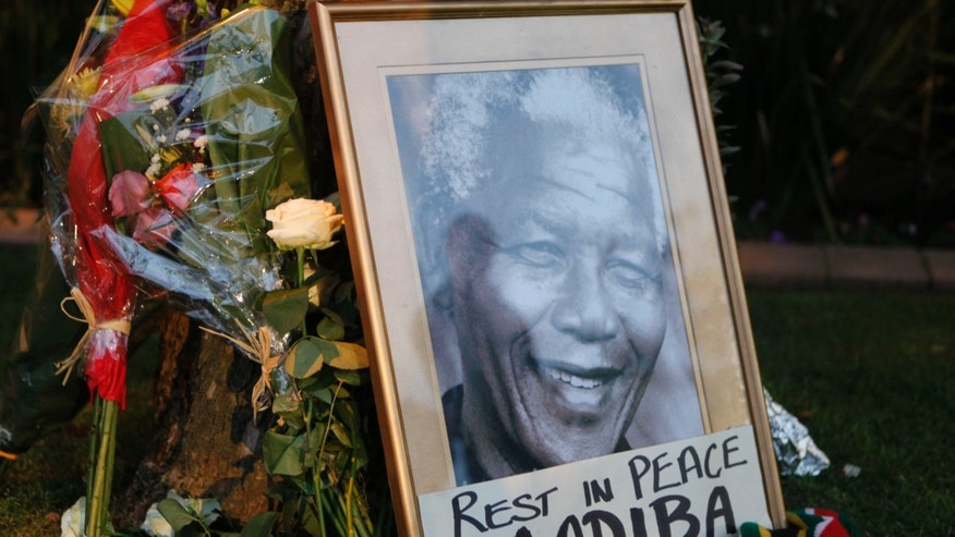 A framed portrait of former president Nelson Mandela and flowers are placed outside Mandela's Johannesburg home Friday, Dec. 6, 2013 after the freedom fighter passed away Thursday night after a long illness. (AP Photo/Denis Farrell)