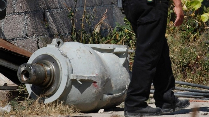 A firefighter stands next to the radiation head that was part of a radiation therapy machine, in Hueypoxtla, Mexico.