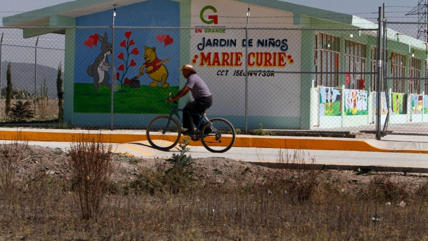A man rides past the Marie Curie kindergarten, across the street from a house where authorities found stolen obsolete radiation therapy equipment carried there by a family who found it nearby in the village of Hueypoxtla, Mexico, Thursday, Dec, 5, 2013. National nuclear safety officials were engaged Thursday in the delicate task of recovering a stolen shipment of highly radioactive cobalt-60 presumed to be found in this rural field in central Mexico state. The missing shipment of radioactive cobalt-60 was found Wednesday near where the stolen truck transporting the material was abandoned in central Mexico. (AP Photo/Marco Ugarte)