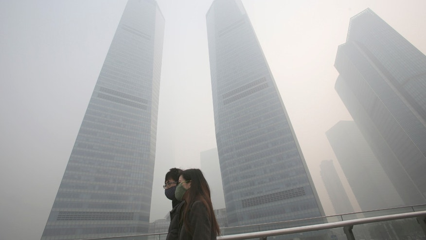 Dec. 6, 2013 - A couple in protective masks walk under haze in Shanghai, China. Shanghai suffered one of its worst bouts of air pollution, bringing visibility down to a few dozen meters and obscuring the city's spectacular skyline.