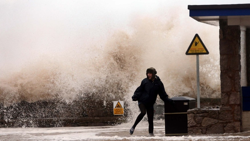 Dec. 5, 2013 - A woman stands in front of a huge wave on the seafront,  in Rhyl, Wales. Gale-force winds hit Scotland Thursday, causing a fatal truck accident, halting all trains and leaving tens of thousands of homes without electricity.