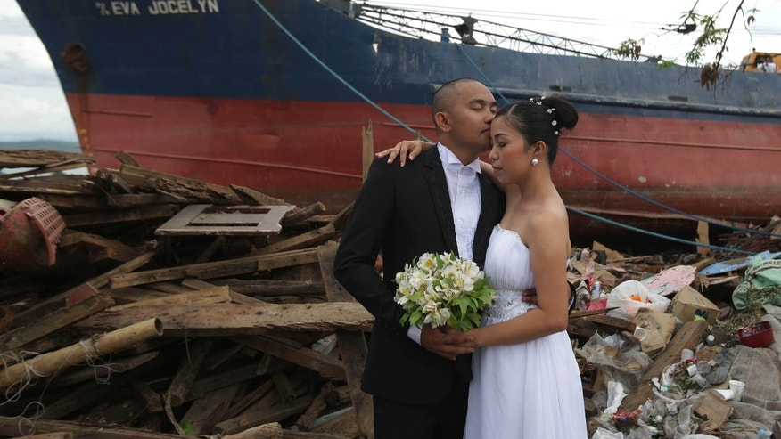 "Filipino groom Earvin Nierva, left, kisses his bride Riza as they pose for their wedding pictures beside damaged homes and a ship that was washed ashore when Typhoon Haiyan hit Tacloban city, central Philippines on Saturday, Dec. 7, 2013. The newly-wed couple decided to have the photo shoot at the area to symbolize that they can overcome tragedy and to urge residents to ""stand up and rise again."" They are residents of Tacloban and also victims of the typhoon. (AP Photo/Aaron Favila)"