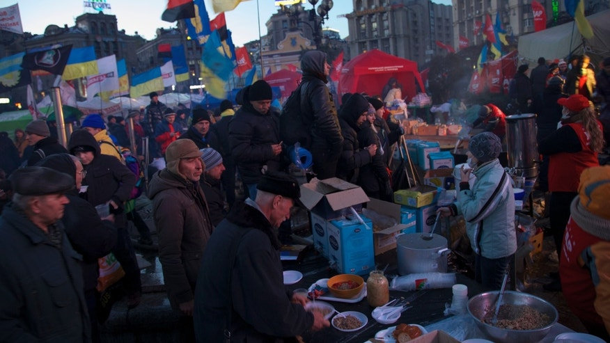 Protesters receive food at a tent camp at central Independence square in Kiev, Ukraine, on Friday, Dec. 6, 2013. As the West called for calm, the government issued threats, and protest leaders frantically searched for a realistic plan of action, thousands of protesters have dug in on Kiev's Independence Square, the site of the 2004 Orange Revolution protests. A solution to Ukraine's deepening political crisis appeared increasingly elusive, but the activists seemed to have everything they need to keep up the revolutionary flame: tents, field kitchens, portable toilets, a giant stage, army veterans at their defense and even the help of psychologist. (AP Photo/Ivan Sekretarev)