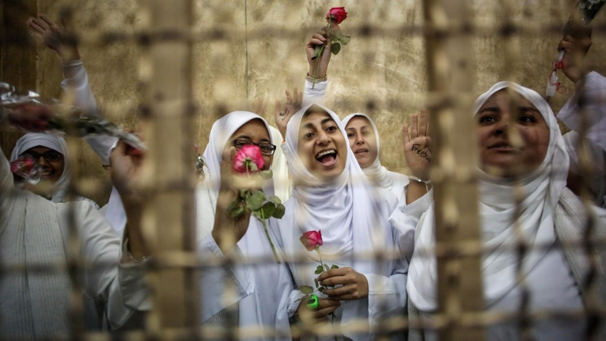 Egyptian women supporters of ousted President Mohammed Morsi stand inside the defendants' cage in a courtroom in Alexandria, Egypt, Saturday, Dec. 7, 2013. A defense lawyer says an Egyptian appeal court has sentenced 14 women to a suspended year for protesting in support of Islamist ousted President Mohammed Morsi, overturning a harsh sentence of 11 years that has caused an outcry.(AP Photo/Eman Helal)