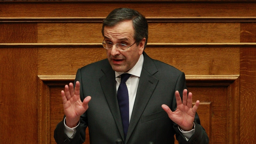 Greek Prime Minister Antonis Samaras delivers a speech during a parliament meeting for a vote on 2014 country's budget in Athens, on Saturday, Dec. 7, 2013. Greece is struggling to complete its latest round of negotiations with bailout lenders, with the pace of staff cuts among the issues that must be resolved and ultimately allow Greece to qualify for long term debt-relief from its creditors. The government is predicting a modest return to growth next year after a six-year recession that erased more than a fifth of its output and left the national debt at around 175 percent of its gross domestic product. (AP Photo/Kostas Tsironis)